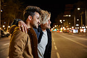 istock Friends talking while walking on street at night 695407616