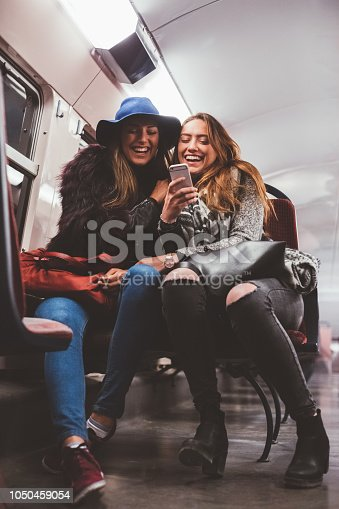 Two women sitting in the train and having fun while texting on smartphone