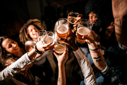 Excited friends toasting with beer glasses at pub