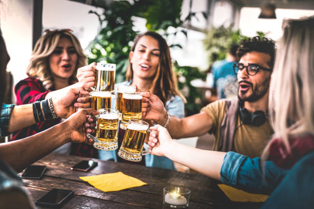 Friends toasting beer at brewery bar indoor at rooftop party - Friendship concept with young people having fun together drinking at happy hour promotion - Focus on glasses - Warm vignetting filter stock photo