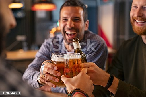 istock Friends toasting beer glass and bottle 1194844801