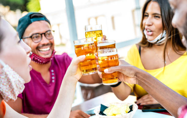 Friends toasting beer glasses with opened face masks - New normal lifestyle concept with people having fun together drinking on happy hour at brewery bar - Bright warm filter with focus on brew pints stock photo