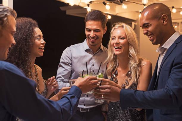amigos tostado cóctel por la noche fiesta - cóctel fotografías e imágenes de stock