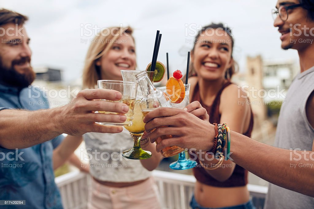 Friends toasting cocktails at a party stock photo