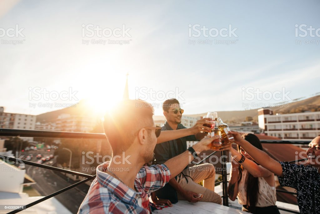 Friends toasting drinks at rooftop party stock photo