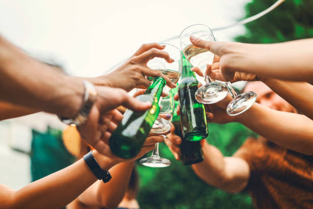 Friends toasting drinks in yard at dinner party stock photo