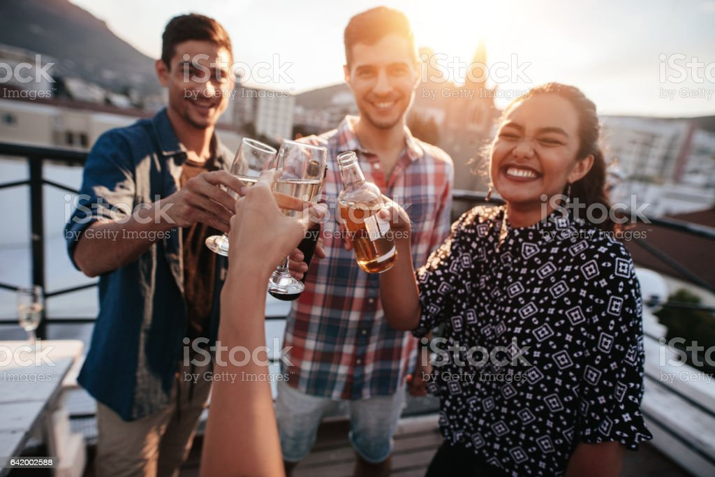 Friends toasting drinks on a rooftop stock photo