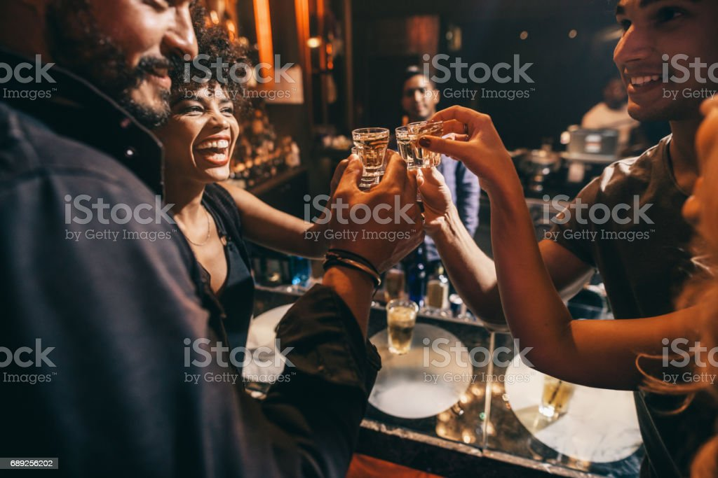 Friends toasting each other with shots of vodka stock photo