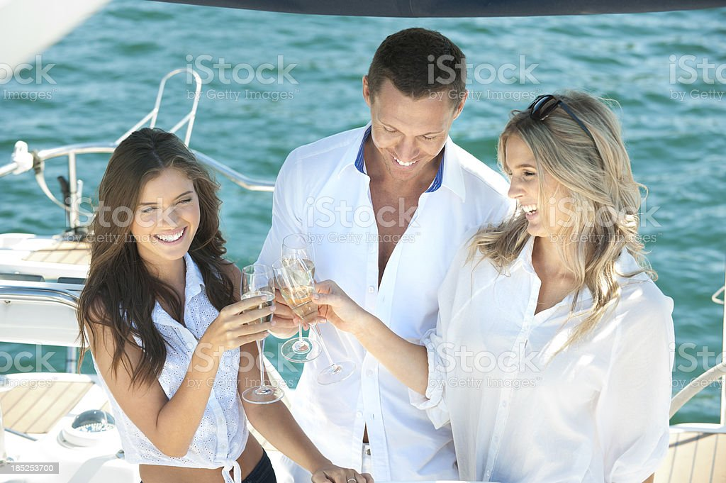 Friends toasting on a glamorous sailing boat royalty-free stock photo