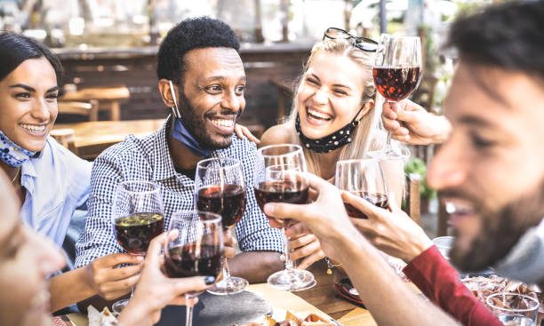 Friends toasting red wine at outdoor restaurant bar with open face mask - New normal lifestyle concept with happy people having fun together on warm filter - Focus on afroamerican guy stock photo