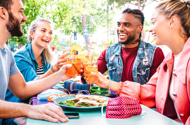 Friends toasting spritz at open air cocktail bar restaurant - Life style concept with young people having fun together sharing drinks on happy hour at garden party - Bright vivid filtered color tones stock photo