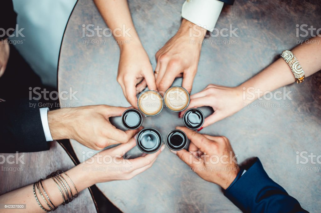 friends toasting with a liqueur shots above round table stock photo