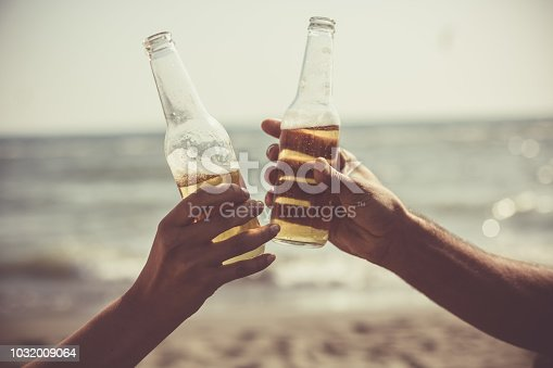 istock Friends toasting with beer bottles at the beach 1032009064