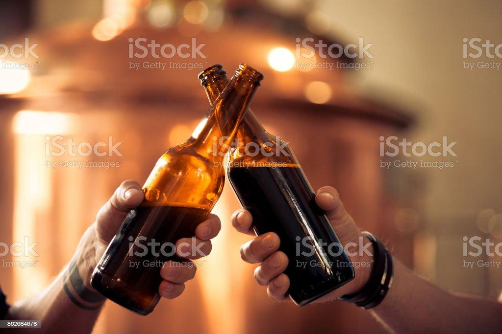 Amigos brindando com garrafas de cerveja na microcervejaria - foto de acervo