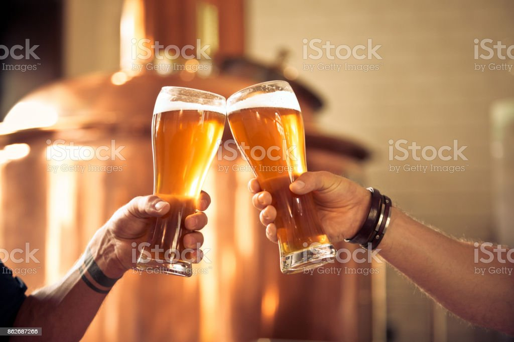 Friends toasting with beer glasses in the microbrewery Friends toasting with beer glasses in the microbrewery. Close up of glasses and hands, unrecognizable people. Copper vat in the background. Adult Stock Photo