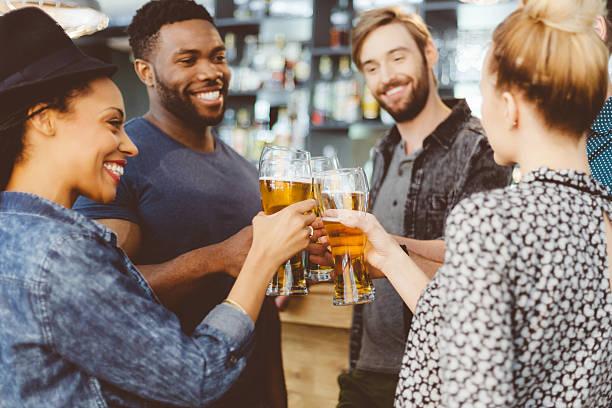 Amis portant un toast à la bière dans un pub - Photo