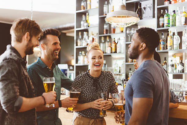 Friends toasting with beer in a pub stock photo