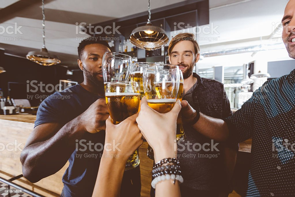 Friends toasting with beer in a pub royalty-free stock photo