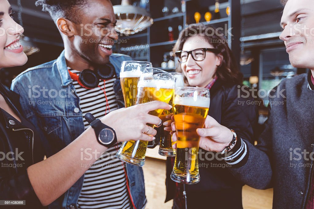 Friends toasting with beer in a pub Multi ethnic group of happy friends - caucasian and afro american - toasting with beer glasses in the pub. Adult Stock Photo