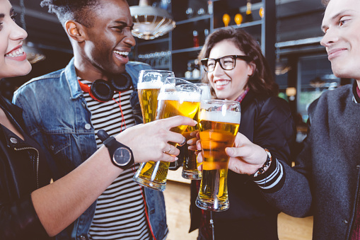 Friends Toasting With Beer In A Pub Stock Photo - Download Image Now