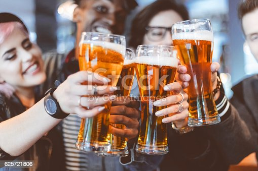 Multi ethnic group of happy friends - caucasian and afro american - toasting with beer glasses in the pub. Close up of hands and beer glasses.