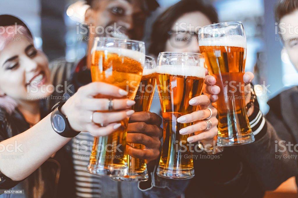 Amigos brindando cerveja em um pub com - foto de acervo