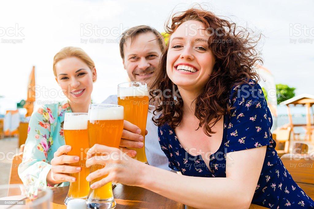 Friends toasting with beer in garden restaurant stock photo