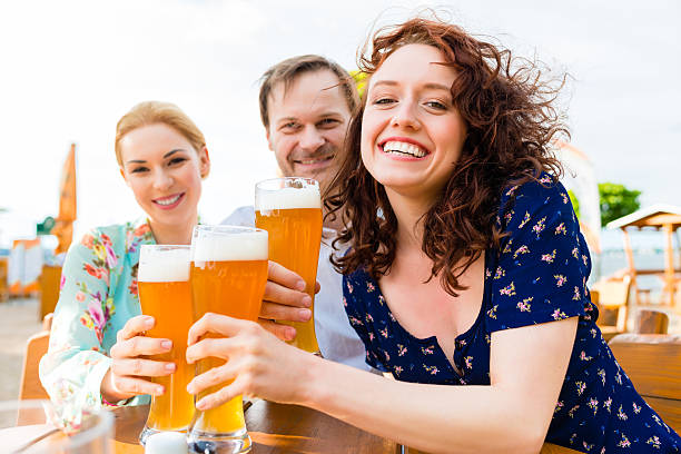 Friends toasting with beer in garden restaurant stock photo