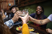 Group Of cheerful People Toasting at pub with fresh beer