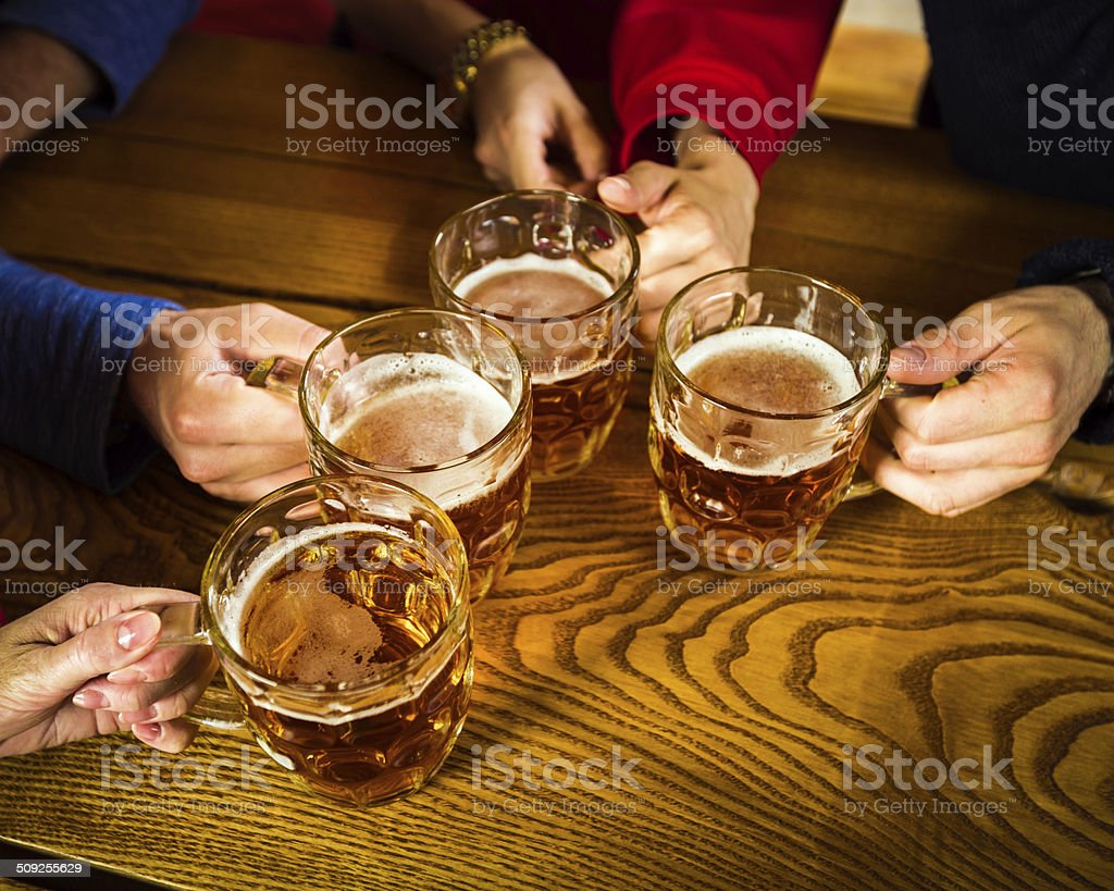 Friends toasting with beer High angle view of group of friends toasting with beer. Close up of beer glasses and hands. Adult Stock Photo
