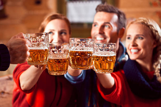 Friends toasting with beer Group of friends wearing warm clothes toasting with beer. Focus on beer glasses. apres ski stock pictures, royalty-free photos & images