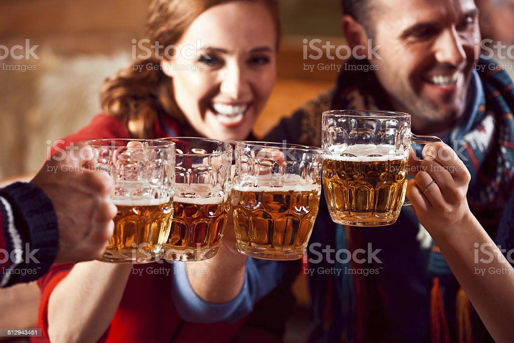 Friends toasting with beer Group of friends sitting in the pub and toasting with beer. Focus on beer glasses. Adult Stock Photo