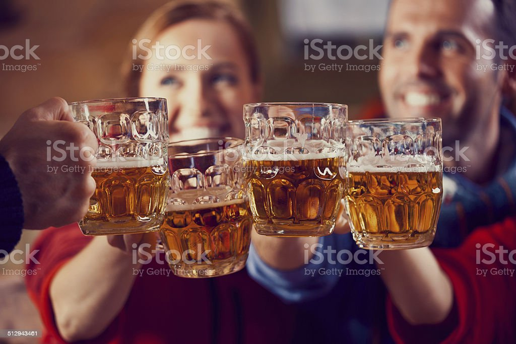 Friends toasting with beer Group of friendssitting in the pub and toasting with beer. Focus on beer glasses. Adult Stock Photo