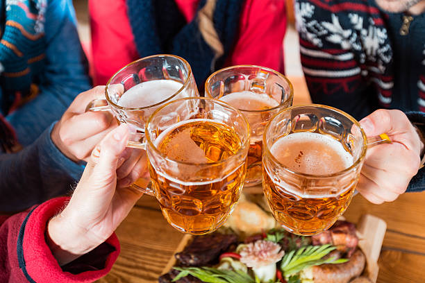 Friends toasting with beer High angle view of group of friends toasting with beer. Close up of beer glasses and hands. apres ski stock pictures, royalty-free photos & images