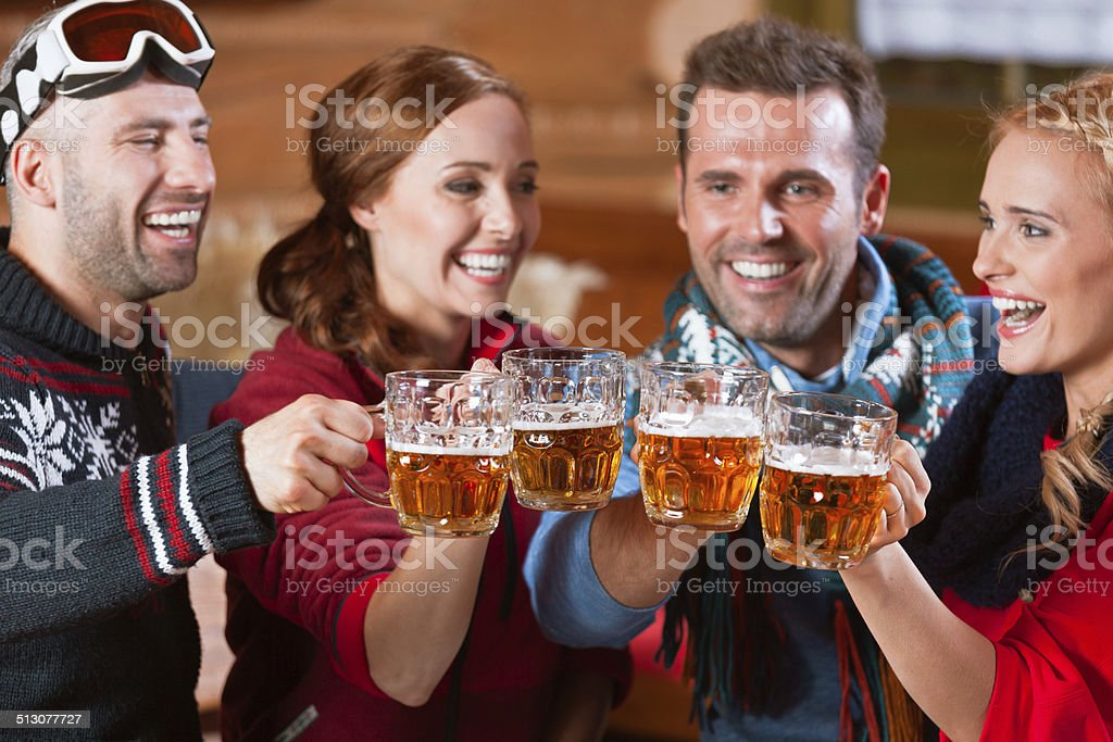 Friends toasting with beer Group of friends sitting in the mountain restaurant after skiing and toasting with beer. Adult Stock Photo