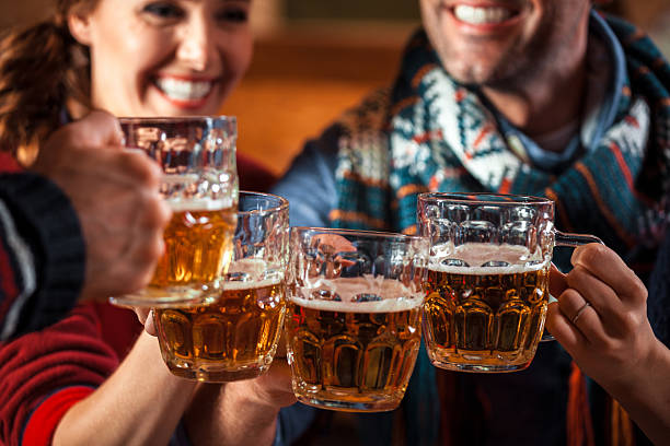 Friends toasting with beer Group of friends sitting in the pub and toasting with beer. Focus on beer glasses. apres ski stock pictures, royalty-free photos & images