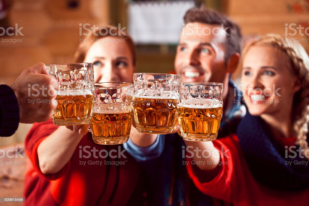 Friends toasting with beer Group of friends wearing warm clothes toasting with beer. Focus on beer glasses. Adult Stock Photo