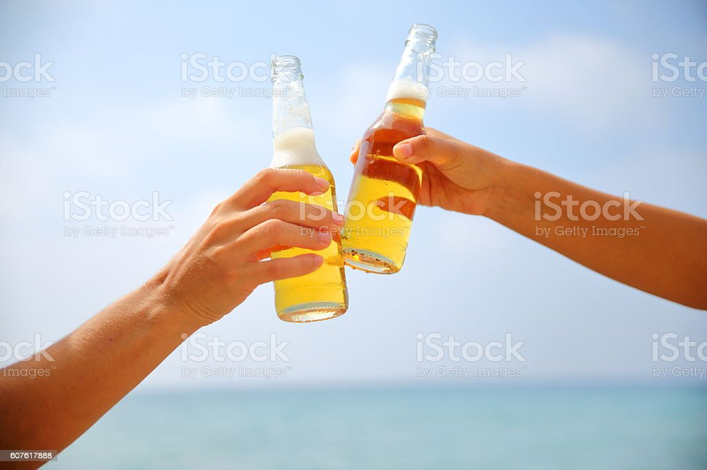 Friends toasting with bottles stock photo