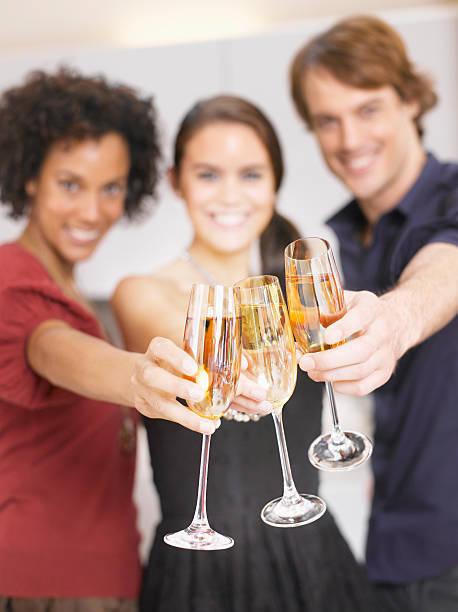 freunden anstoßen mit champagner auf party - jamaikanische party stock-fotos und bilder