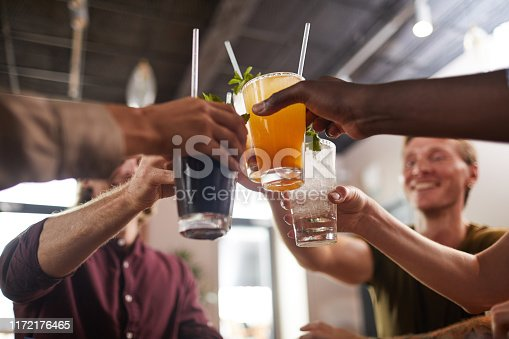 Low angle closeup of friends clinking glasses while sitting at table in cafe enjoying cold refreshing drinks, copy space