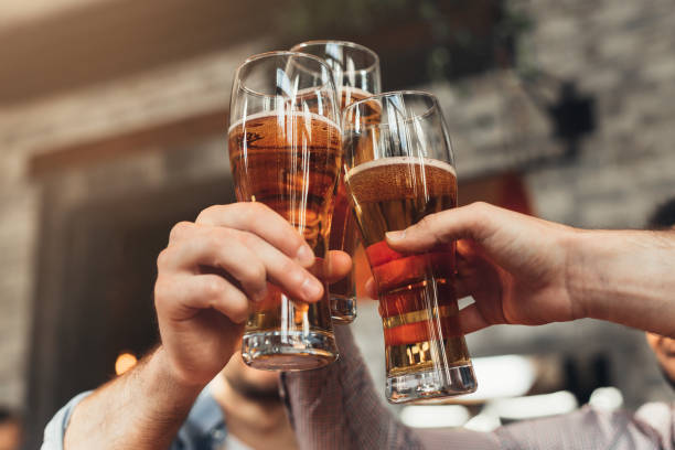 friends toasting with glasses of beer at the pub - , beer foto e immagini stock