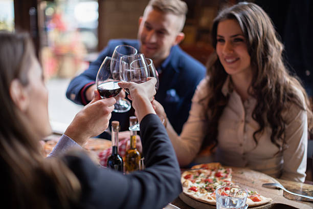 friends toasting with red wine - pizzeria stock photos and pictures