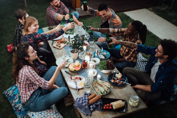 friends toasting with wine and beer at rustic dinner party - foodie stock photos and pictures