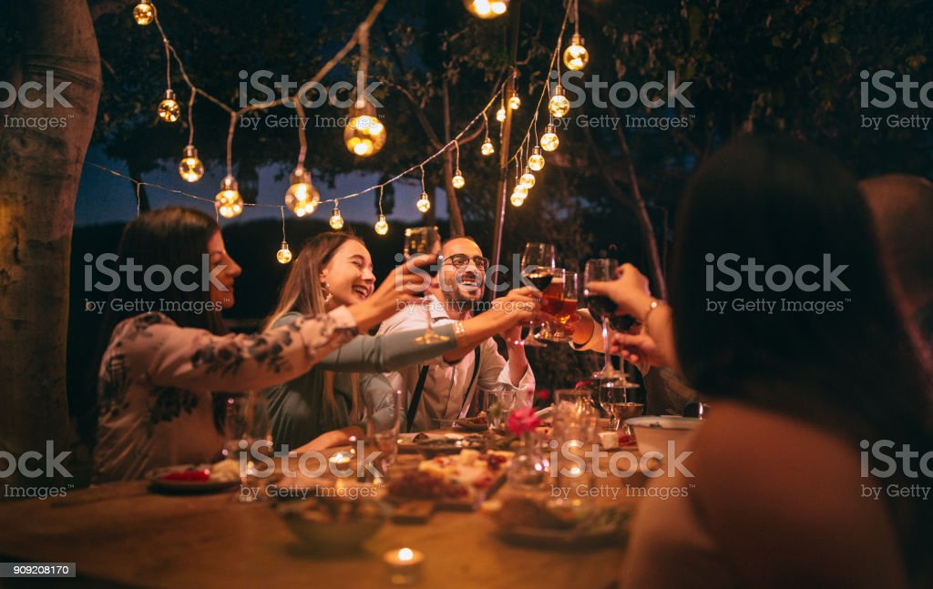 Friends toasting with wine and beer at rustic dinner party stock photo