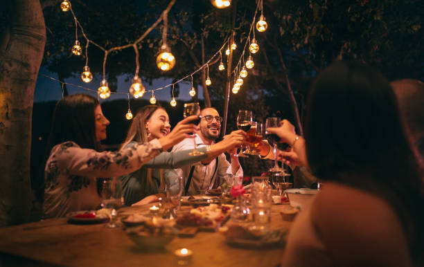 Friends toasting with wine and beer at rustic dinner party - foto stock