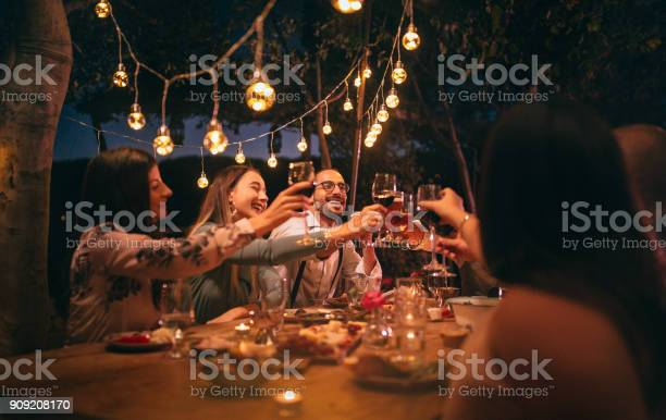 Happy young friends having fun and toasting around mediterranean dinner party table in Italian countryside