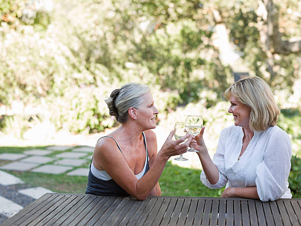 Friends toasting with wine outdoors stock photo