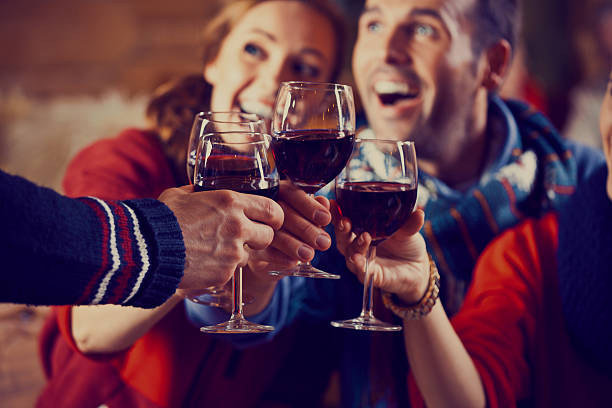 Friends toasting with wine Group of friends wearing warm clothes toasting with red wine. Focus on wine glasses. apres ski stock pictures, royalty-free photos & images