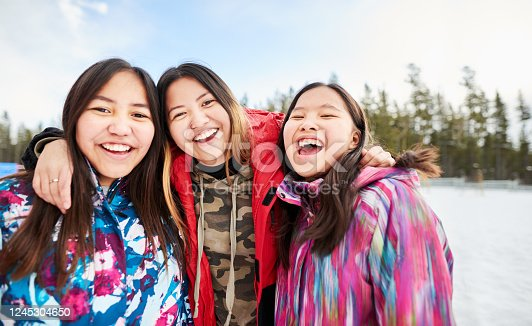 Portrait of young school girls in warm clothing looking at camera and smiling in the winter