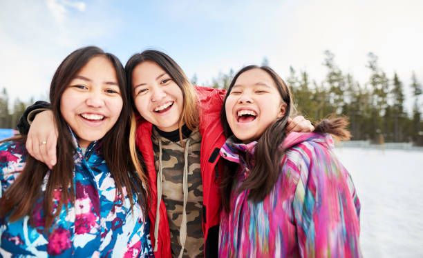 Friends together at recess Portrait of young school girls in warm clothing looking at camera and smiling in the winter indigenous peoples of the americas stock pictures, royalty-free photos & images